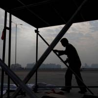 A laborer erects scaffolding in the Chinese megalopolis of Guangzhou on Nov. 23. | BLOOMBERG