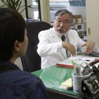 Dr. Kim Seok-kwun talks with a patient at Dong-A University Hospital in Busan, South Korea, on March 18. | AP
