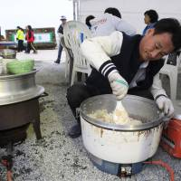 Lim Jang-young, 58, a volunteer and the owner of a Japanese restaurant in the southern city of Daejon, helps prepare meals for relatives of missing passengers who were aboard the ferry Sewol in Jindo, South Korea, on Saturday. | AP