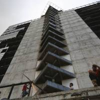 The 45-story 'Tower of David,' seen Feb. 3 from the 30th floor, was intended to be a shining new financial center in the heart of Caracas but it was abandoned in 1994 after the developer's death. Squatters in 2007 invaded the huge concrete skeleton, turning it into the highest slum in the world. It now houses 3,000 people.   REUTERS