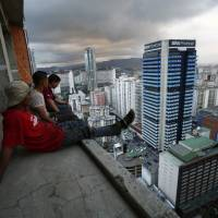 A group of men take in the view of Venezuela's capital after salvaging metal on the 30th floor of the 'Tower of David' in central Caracas on Feb. 3. | REUTERS