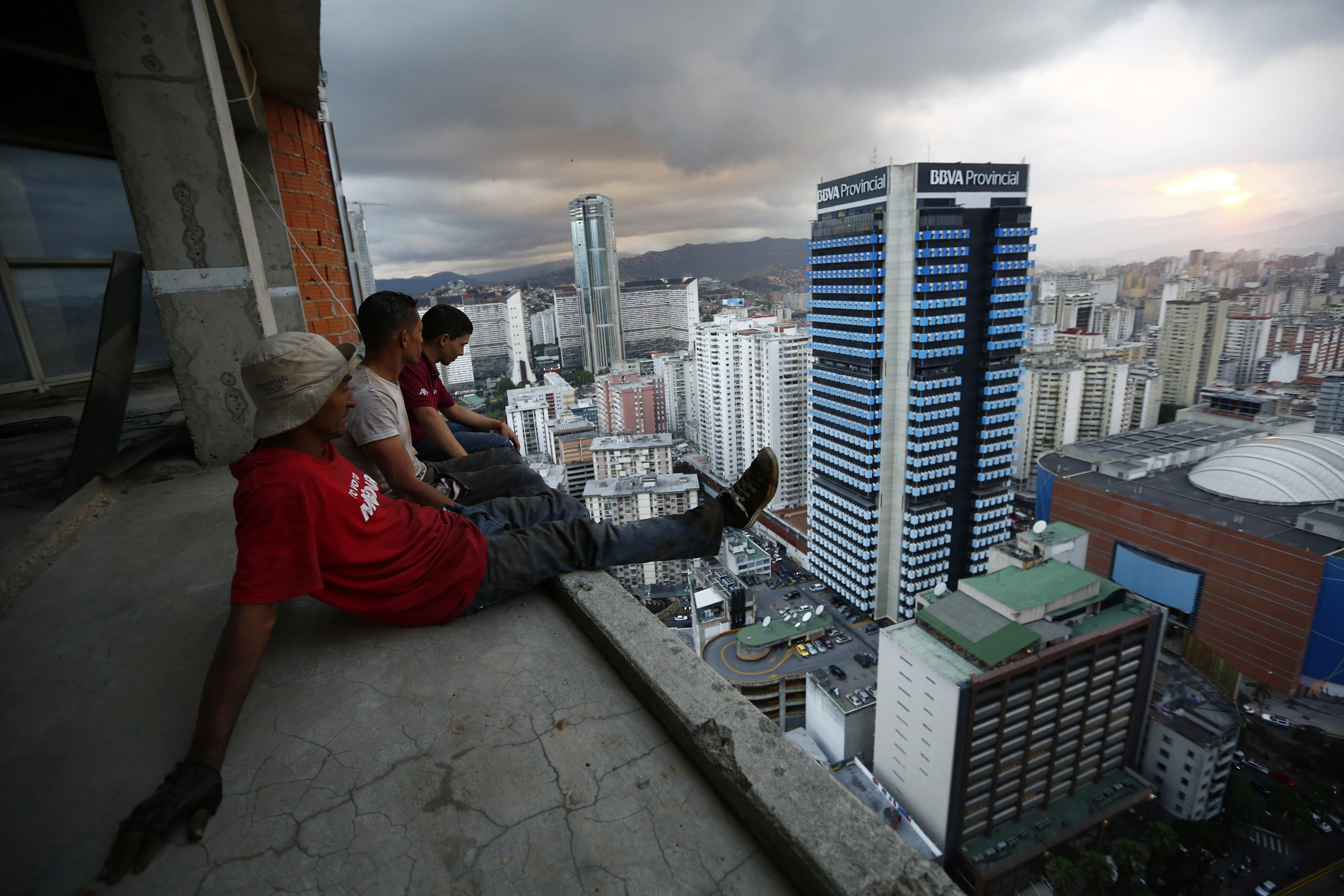 A group of men take in the view of Venezuela's capital after salvaging metal on the 30th floor of the 'Tower of David' in central Caracas on Feb. 3.   REUTERS