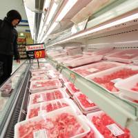 A shopper looks at packaged U.S. beef at a Seiyu GK supermarket in Tokyo last year. | BLOOMBERG