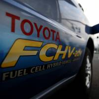 A hydrogen nozzle is plugged into a Toyota Fuel Cell Hybrid Vehicle during the Toyota Advanced Technologies media briefing in Tokyo on Oct. 10. | REUTERS
