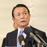 Finance Minister Taro Aso answers questions from reporters in Washington on Thursday.   KYODO