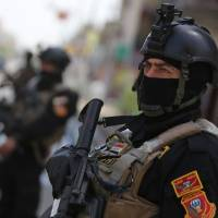 Anti-terrorism forces stand guard outside a polling station in Baghdad on Tuesday, a day ahead of Iraq's first general election since U.S. troops withdrew from the country. | AFP-JIJI
