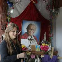Floribeth Mora, who recovered from a brain aneurysm, stands by her shrine to Pope John Paul II at her home in La Union de Cartago, Costa Rica, last July 5. | AP