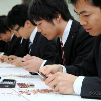 Newly hired employees of Mitsubishi Pencil Co. learn how to sharpen pencils with a knife as part of the firm's welcoming ceremony at its head office in Shinagawa Ward, Tokyo, on Tuesday. The event was first held in 2008 so new hires could familiarize themselves with the company's products. | SATOKO KAWASAKI