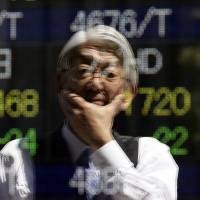 A man is reflected in an electronic stock quotation board Friday outside a Tokyo brokerage. | REUTERS