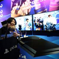 A customer holds a bag with a new PlayStation 4 video game console inside after purchasing it at Sony's showroom in Tokyo on Feb. 22. | BLOOMBERG