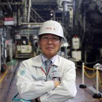Mitsuru Kawai, senior technical executive at Toyota Motor Corp., poses in the forging department at one of the automaker's plants in Toyota, Aichi Prefecture, in February. | BLOOMBERG