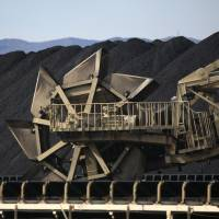 A bucket-wheel excavator moves coal at a stockpiling site at Onahama port in Iwaki, Fukushima Prefecture, in February. With the nation's nuclear power plants out of action, Japan now has to rely on oil-, coal- and gas-fired plants to replace more than 25 percent of its electricity needs lost since the multiple core meltdowns of March 2011. | BLOOMBERG