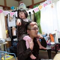 Kazunori Nagai, an Internet media firm manager who is finding it difficult to take paternity leave, spends some rare quality time with his 4-year-old daughter at home in Tokyo on March 2. | BLOOMBERG