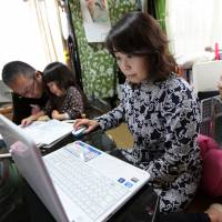 Yuko Nagai works on her computer at home in Tokyo while her husband, Kazunori, plays with their daughter. | BLOOMBERG