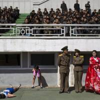 Runners rest inside Pyongyang's Kim Il Sung Stadium when North Korea hosted the 26th Mangyongdae Prize International Marathon to mark the birth date of the country's late founder, Kim Il Sung, in April last year. | AP