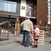 A man and a girl look at a closed McDonald's restaurant in Simferopol on Friday after the fast-food giant shuttered its three stores in Crimea. | AFP-JIJI