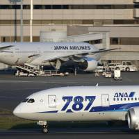 An All Nippon Airways Co. Boeing 787 Dreamliner taxis on the tarmac after landing at Tokyo's Haneda airport in October, while a Japan Airlines Co. jet is parked at a gate. | BLOOMBERG
