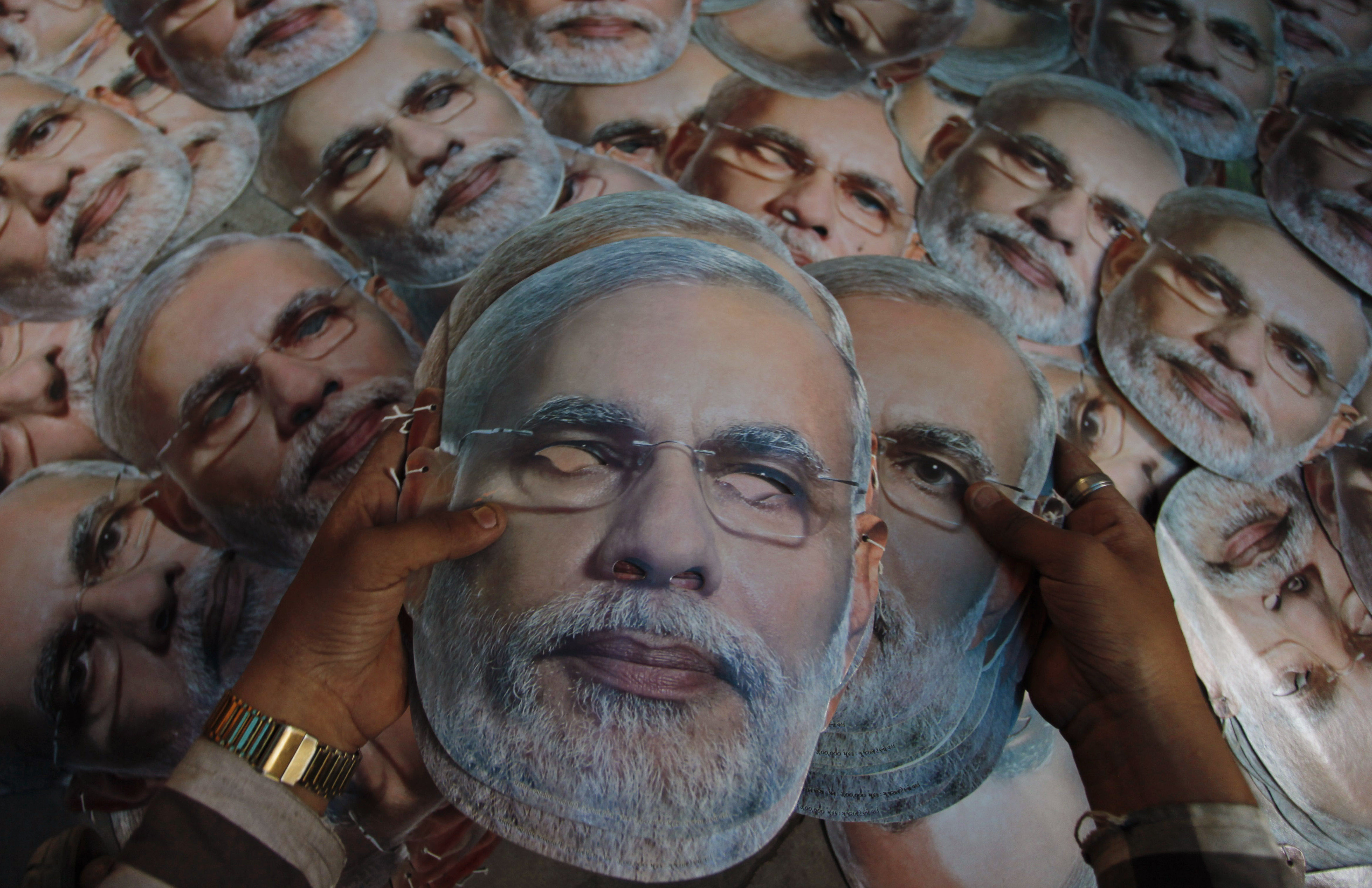 A print shop worker arranges masks depicting Narendra Modi, prime ministerial candidate for the main opposition Bharatiya Janata Party in Indian national elections, at a printing press in Ahmadabad, India, on April 12.   AP