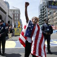 Meb Keflizighi of San Diego, California, celebrates winning the 118th Boston Marathon on Monday in Boston. Keflizighi became the first American to win the men's race in more than 30 years. | AP