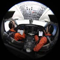 Pilots Makoto Hoshi (left) and Shunichi Yumiza look at notes on Tuesday as they sit in the cockpit of a Japan Coast Guard Gulfstream V aircraft, currently scouring the southern Indian Ocean on the lookout for debris from Flight MH370. | REUTERS