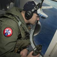 A U.S. naval aircrewman looks out a window of a P-8A Poseidon while flying over the Indian Ocean during a search mission to locate Malaysia Airlines Flight MH370 on Thursday. | REUTERS