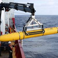 Crew aboard the Australian naval vessel Ocean Shield prepare to deploy the U.S. Navy's Bluefin-21 autonomous underwater vehicle to hunt for the missing Malaysia Airlines Flight MH370 in the southern Indian Ocean on Monday. | REUTERS