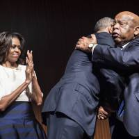 U.S. first lady Michelle Obama watches as President Barack Obama is hugged by Rep. John Lewis at the Lyndon B. Johnson Presidential Library on Thursday in Austin, Texas, during a summit to celebrate the 50th anniversary of the Civil Rights Act of 1964.   AFP-JIJI