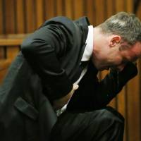South African Paralympic track star Oscar Pistorius vomits as he listens to evidence by a pathologist during his trial at a Pretoria court Monday.   AFP-JIJI
