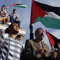 Palestinians in the Gaza City on Wednesday wave national flags as they celebrate following an announcement of a reconciliation agreement between the Gaza Strip-based Islamist group Hamas and President Mahmoud Abbas's Palestine Liberation Organization. | REUTERS