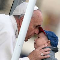 Pope Francis kisses a young boy upon his arrival at the Vatican's St. Peter's Square during his weekly general audience on Wednesday.   AFP-JIJI
