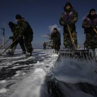 Crew members wash the flight deck of the USS Ronald Reagan in an attempt to remove radiation deposits on March 23, 2011. Sailors aboard the aircraft carrier, in the Pacific Ocean off the coast of Tohoku, had taken part in a rescue mission transporting supplies to evacuees and survivors following the Great East Japan Earthquake and tsunami.   AP