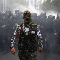 A pro-Russian protester walks in front of riot police during a pro-Ukraine rally in the eastern city of Donetsk on Monday. | REUTERS