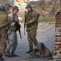 Ukrainian Army troops take positions at an airport in Kramatorsk, eastern Ukraine, on Tuesday. In the first Ukrainian military action against a pro-Russian uprising in the east, government forces clashed Tuesday with about 30 armed gunmen at a small airport in the city. | AP