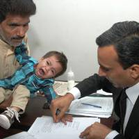 A Pakistani lawyer takes a thumb impression from 9-month-old Mohammad Musa on a bail bond in Lahore. The infant has been accused of attempted murder along with his father and other relatives for throwing rocks at gas company officials Feb. 1. | AFP-JIJI