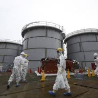 Tokyo Electric Power Co. employees and media crews wear protective suits while walking past storage tanks for radioactive water during a tour of the Fukushima No. 1 power plant last November. | REUTERS