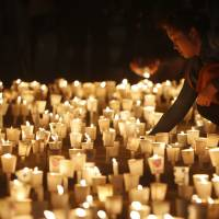 A woman attends a candlelight vigil in Ansan on Thursday to commemorate victims of the South Korean passenger ship Sewol, which capsized and sank last week off the country's southwest coast. | REUTERS