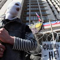 A pro-Russian activist guards a barricade in front of the Donetsk regional administration building on Tuesday. | AFP-JIJI