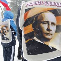 Russians wear vests emblazoned with images of President Vladimir Putin during a rally in Stavropol on Saturday.   REUTERS