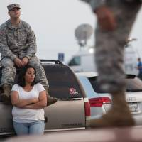 Spc. Timothy Hamlin and his wife, Lucy Hamlin, wait for permission to re-enter the military base at Fort Hood, Texas, where they live, following a shooting at the site Wednesday that left four people dead and injured 14 others.   AP
