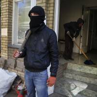 A masked pro-Russian militant guards a seized police station in the eastern Ukrainian city of Slovyansk on Friday. | AP