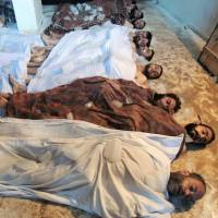 In this Aug. 21, 2013, photograph provided by Shaam News Network and subsequently authenticated based on its contents, bodies are laid out following a chemical weapons attack by the Syrian regime force members against the rebel-held Damascus suburb of Ghouta.   AP