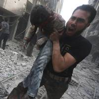 A man carries a body at a site hit by what activists said was an attack by regime warplanes in the Duma neighborhood of Damascus on Sunday. | REUTERS