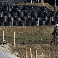 A man walks near waste containing radiated soil, leaves and debris from a decontamination operation at a storage site in the Miyakoji district in Tamura, Fukushima Prefecture, on April 1. | REUTERS