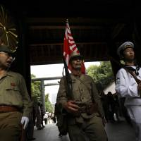 Visitors wearing Imperial Japanese Army and Navy uniforms enter Tokyo's Yasukuni Shrine, which honors Japan's war dead — including convicted Class-A war criminals — during a ceremony marking the 65th anniversary of the end of World War II on Aug. 15, 2010. | AP