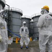 A Tokyo Electric Power Co. official (center) and journalists wearing protective suits and masks are seen standing near the H4 tank at Fukushima No. 1 nuclear power plant in Okuma, Fukushima Prefecture, last November. Radioactive water leaked from a storage tank in August. | AP