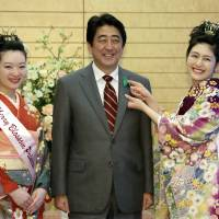 Prime Minister Shinzo Abe is all smiles as he welcomes Japan Cherry Blossom Queen Mamiko Watanabe, 19 (right), and Japan Cherry Blossom Princess Michiko Tani, 19, during a visit to the prime minister's official residence in Tokyo on Monday. Ahead of an April 23-25 visit by U.S. President Barack Obama, Abe's administration has moved closer to the remaining gaps over the Trans-Pacific Partnership free trade pact, and top officials from both sides will meet in Tokyo on Monday. | AP