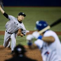 So it begins: Yankees starter Masahiro Tanaka pitches to the Blue Jays' Melky Cabrera in the first inning on Friday in Toronto. Tanaka earned the win in his MLB debut.   AP