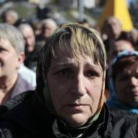 A woman cries during a rally to honor the memory of those who were killed during mass protests in Kiev, on the Ukrainian capital's Independence Square on Sunday. | AP