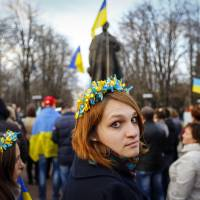 A woman wearing a flower crown looks back during a pro-Ukrainian rally in the eastern city of Luhansk on Tuesday. | AFP-JIJI