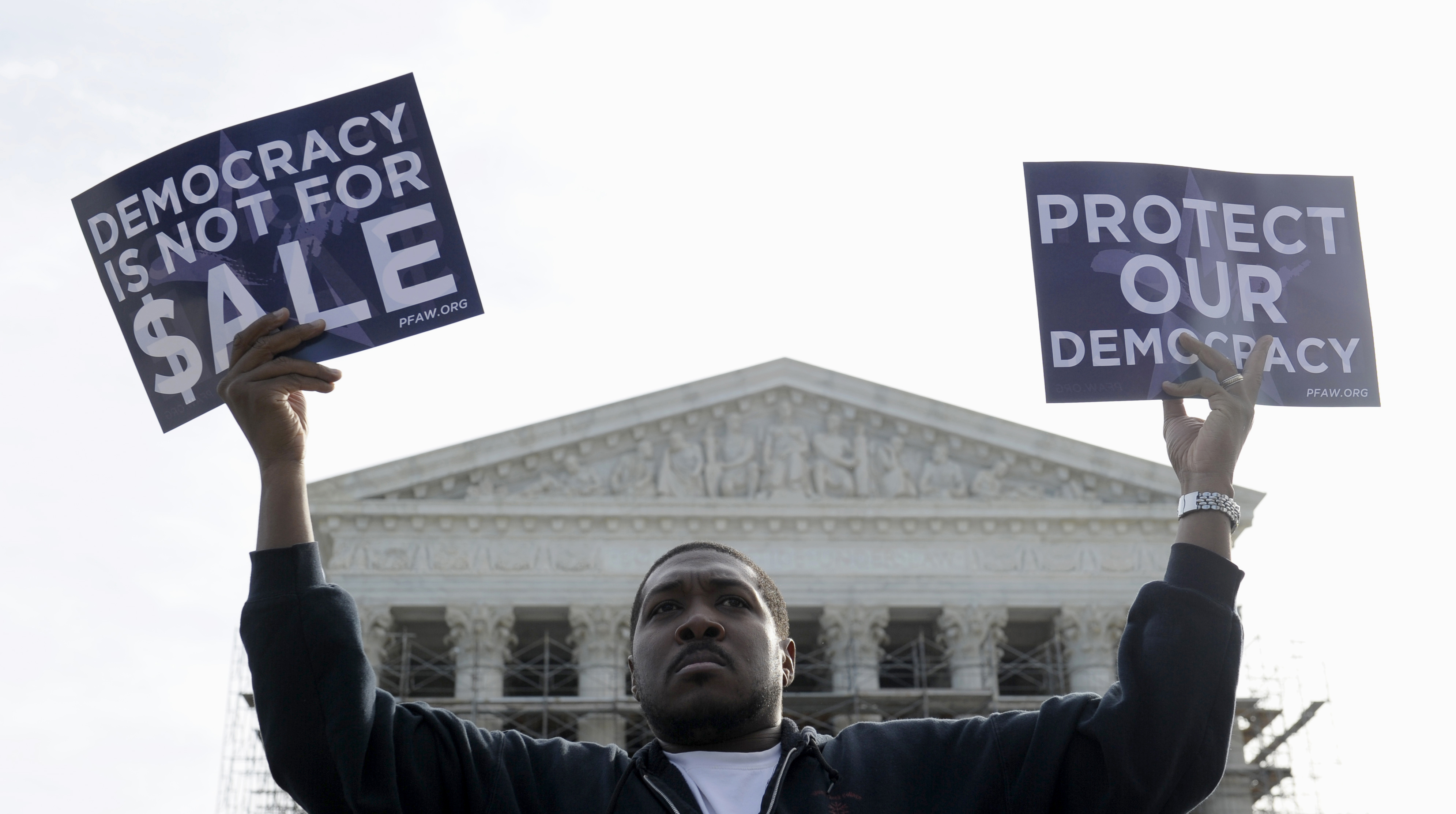 A demonstrator takes part in a rally outside the Supreme Court in Washington as the court heard arguments on campaign finance on Oct. 8, 2013. In a 5-4 vote Wednesday, the court struck down limits in federal law on the overall campaign contributions the biggest individual donors may make to candidates, political parties and political action committees. | AP